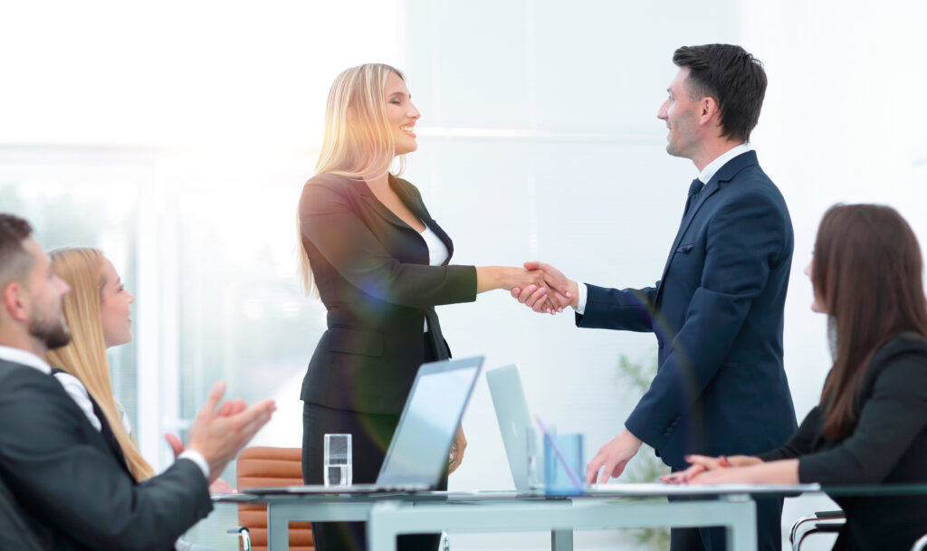 handshake business partners after discussion of the contract standing over a Desk.